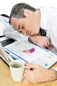 Tired businessman fell asleep at his desk while looking for sleep references